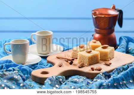 Semolina halva with whole almonds served with geyser coffee maker on blue embroidered cloth. Homemade Indian sweets with blue background