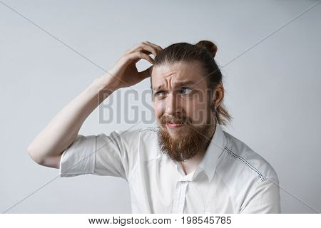 Picture of confused and puzzled young Caucasian office worker with beard and hair knot scratching his head having clueless and worried look trying hard to recollect something. Body language