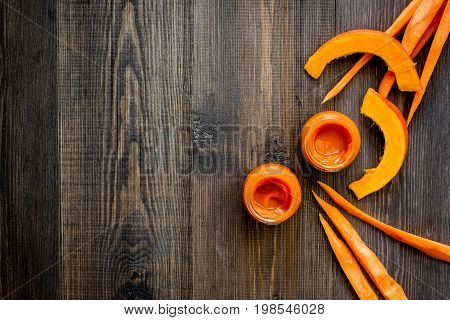 Baby food. Pumpkin puree on dark wooden table background top view.