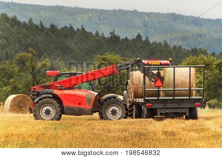 Telescopic collector straw collector on field in the Czech Republic. Work on an agricultural farm. Collecting straw bales
