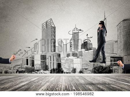 Businessman with blindfolder on eyes walking on rope