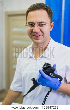 happy proctologist holding anoscope at hospital ward .
