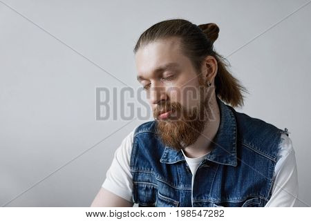 Close up shot of handsome stylish young unshaven male with hair knot and earring keeping his eyes closed having calm and peaceful facial expression taking nap or sleeping trying to relax after work