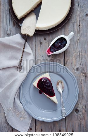 Homemade cheesecake with berry sauce on a gray plate