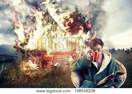 Man drinks coffee and reading a book while his house is on fire on a mountain background. Concept of a careless man.