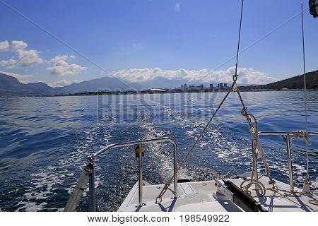View from the stern of the sailboat while sailing away from the harbor