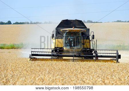 Kharkiv Region Ukraine - July 25 2017: Combine harvest wheat on a field in sunny summer day in Kharkiv Region Ukraine on July 25 2017.