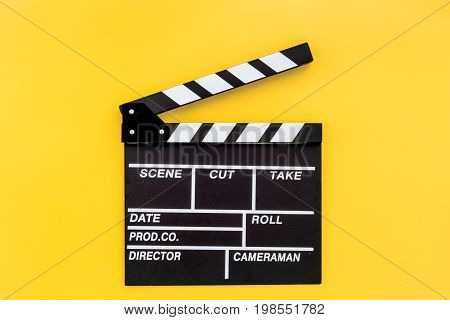 Filmmaker profession. Clapperboard on yellow background top view.