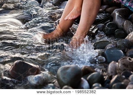 Summer holidays, Vacation concept. Family sitting on pebble beach in water. Bare feet.