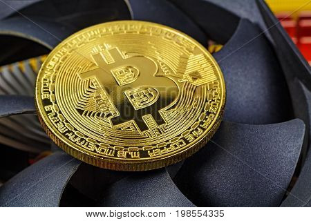 Golden Bitcoin On The Central Processing Unit Fan Background Closeup. Cryptocurrency Virtual Money