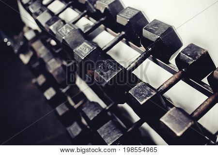 lot of dumbbells stand in row in the gym, glare of light. Concept slimming, musculature, bodybuilding, Sports Equipment.