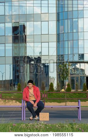 A homeless guy sits on the bench with a cardboard and an inscription: need money. In the background is a business center.