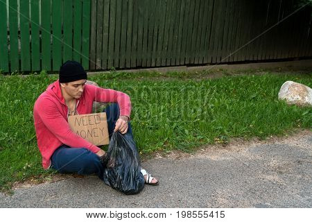 A homeless guy sits on the sidewalk with a cardboard and an inscription: need money.