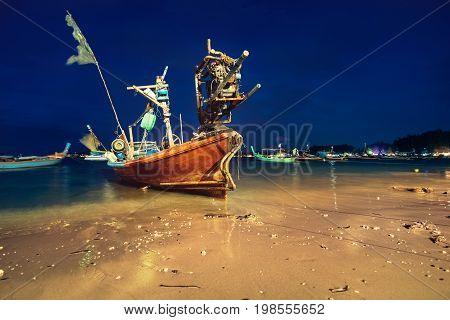 Silhouette of traditional longtail boat at the shore after sunset, BangTao beach, Phuket island. Romantic outdoor photography on a night beach with traditional thai boats floating in water, Thailand