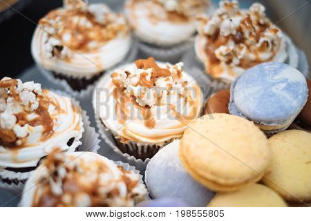 Fresh baked macaroon pastry cookies macarons, macaroni and cupcakes with caramel cream. Candy bar for birthday patry celebration, childhood, shallow focus. Sweet table - desserts, macaroni, cake