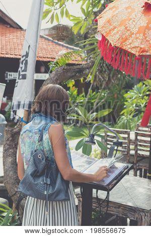 Woman in sunglasses with fashion snakeskin python bag walking on the street. Bali island.