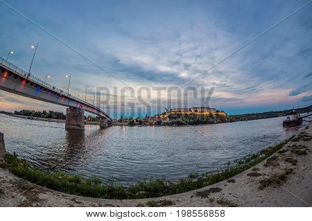 Night view of Rainbow bridge on the river Danube in Novi Sad Serbia with Petrovaradin fortress in background.