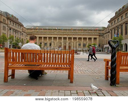 Caird Hall from Dundee. Dundee, Scotland - July 30, 2017 Man on a bench in front of a stylish concert hall auditorium in the Scottish city of Dundee.