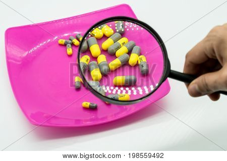 Hand holding magnifying glass looking at medicine capsule on plastic pink dish isolated on white background.