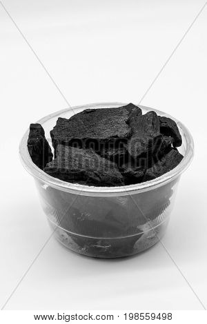 Natural wood charcoal in plastic cup isolated on white background. Traditional charcoal or hard wood materials as odor absorber in refrigerator.