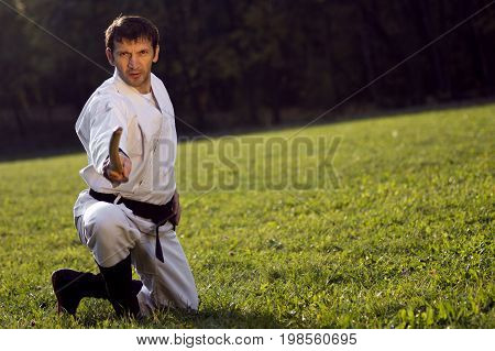 The man in white kimono and black belt is practicing martial arts with wooden sword outdoors on the grass.