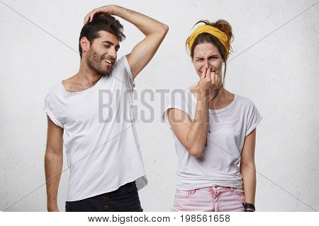 Bad Smell And Body Odor. Picture Of Fastidious Young Woman Pinching Her Nose Disgusted With Terrible