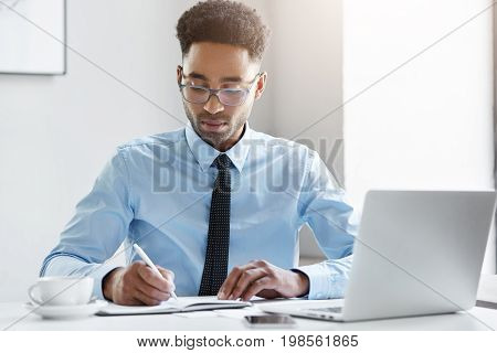 Serious Unshaven Dark-skinned Businessman With Curly Dark Hair, Wearing Glasses, Elegant Shirt And T
