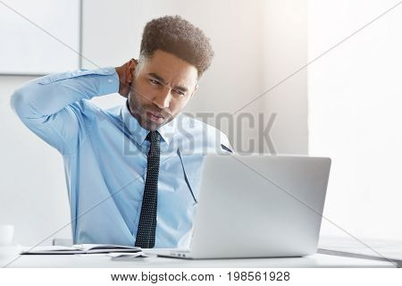Young Financial Director Working On His Business Report, Looking With Tired Expression In His Comput