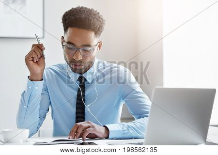 Elegant Employee With Concentrated Look Holding Pen In Hand While Writing Something Looking At His N
