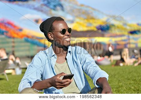 Dark-skinned Hipster Guy In Trendy Shades And Hat, Feeling Relaxation While Sitting At Green Grass W