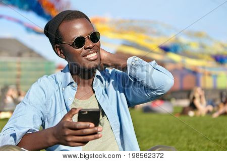 Joyful Afro American Male In Fashionable Clothes Holding Smart Phone In Hand Waiting For Important C