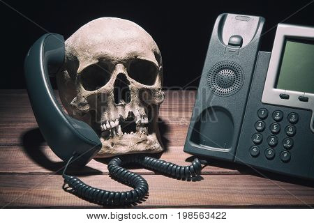 Office work concept. Human skull model with modern telephone on wooden table and black background