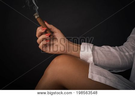 Closeup of woman hand holds tompus cigare on her bare leg. Studio shoot