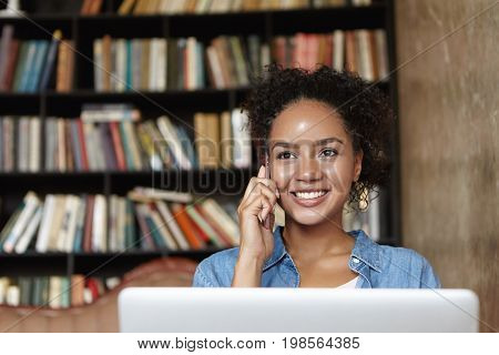 Young Female Adult With Dark Skin And Curly Hair Smiling Broadly While Sitting In Front Of Opened La
