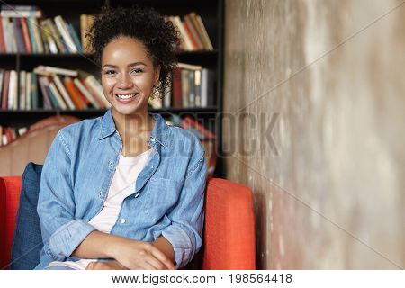 Cute Brunette Mixed Race Woman In Jean Shirt Sitting In Reading Room At Comfortable Armchair, Going