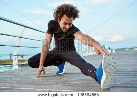 Dark-skinned man athlete in black sportswear and blue sneakers stretching his legs with lunge hamstring stretch exercise on the pier. Afro-American young male runner warming-up his muscles before strength training workout.