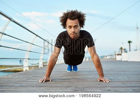 Fit and motivated Afro-American sportsman standing in plank position, stretching on wooden platfom. Dark-skinned sportsman with bushy hair doing yoga at seaside.