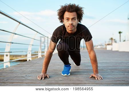 People and healthy lifestyle concept. Fit Afro-American runner with bushy hair wearing running outfit getting ready for workout session behind the sea. Dark-skinned male jogger exercising outdoors.