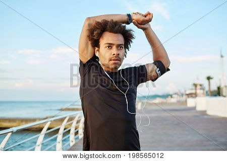 Fit dark-skinned male athlete with bushy hair doing stretching exercises, raising his arms, warming up his muscles before outdoor morning workout session. Afro-American runner stretching his arm muscles.