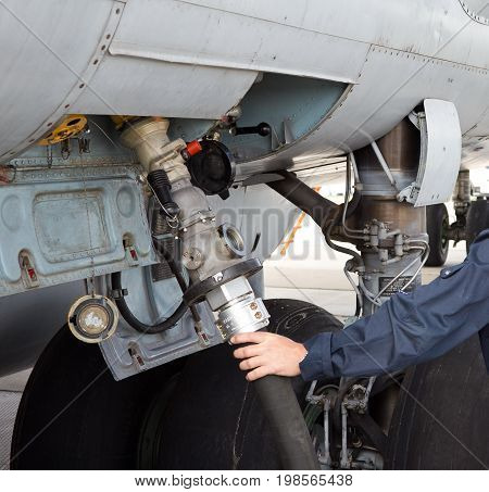 The process of refueling airplane in airport. Fuel hose is inserted. Hand with hose
