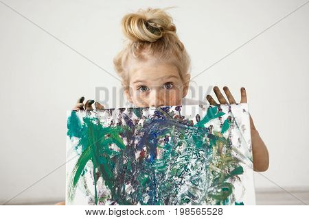Close-up portrait of blonde European little girl with hair bun and big blue eyes demonstrating her picture. Talented kid makes parent feel good. Child is a source of positive emotions.