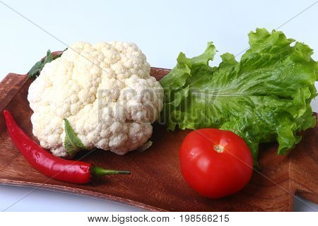 fresh cauliflower, tomato, salad leaves and other vegetables on wooden board. Ready for cooking. Vegetarian food