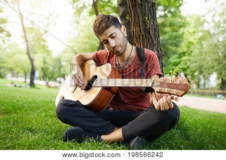 Handsome good-looking male playing musical instrument outdoors. Bearded guy with stylish haircut sitting under the tree with guitar.