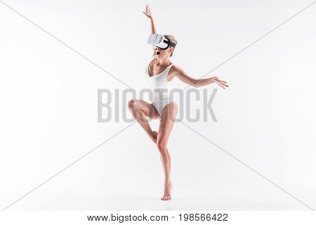 Frightened youthful sporty girl n vr headset is standing on one leg, bending other one. She is stretching hands to sides and opening mouth. Isolated