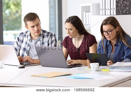 Three attentive employees working on line together with multiple devices at office