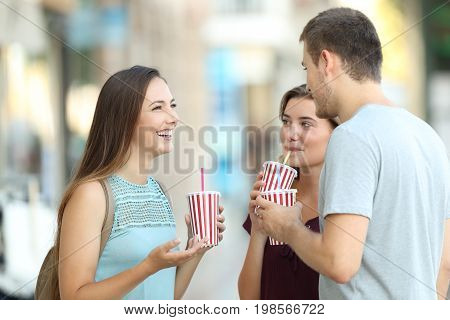 Three happy friends talking and drinking takeaway refreshments standing in the street