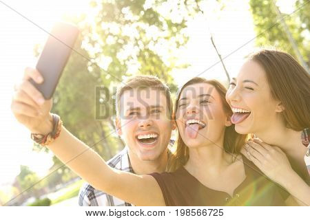 Back light of three funny teens taking selfies and joking in the street