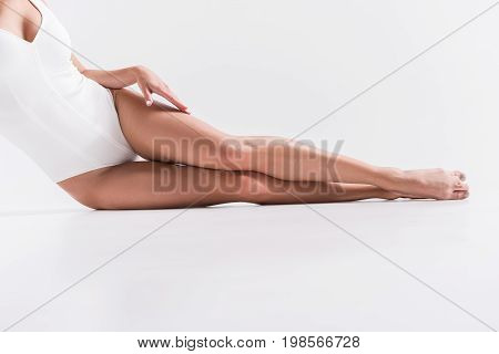 Close up of body and legs of young sporty woman sitting on floor. She is leaning on hip and spreading out her legs straight
