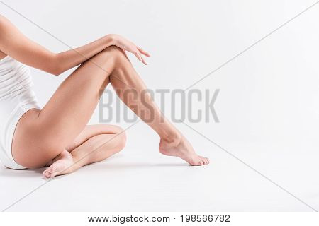 Close up of legs and hand of youthful fit woman in gym suit sitting on floor barefoot. She is putting arm on her knee. Copy space