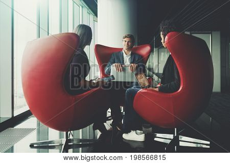 Handsome smiling businessman and two of his female colleagues are sitting on curved red armchairs with gadgets while finishing their work meeting in office interior of business skyscraper near window